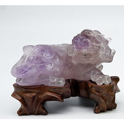 Chinese Carved Amethyst Model of a Buddhist Lion on a Carved Hardwood Stand, 20th Century