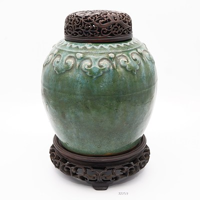 Antique Chinese Green Glazed Stoneware Jar with a Moulded Ruyi Border, Pierced and Carved Hardwood Stand and Cover